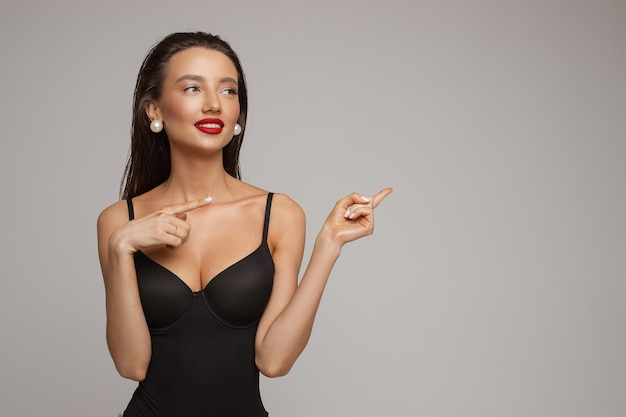 Piękna młoda kaukaska kobieta z długimi ciemnymi włosami, ładnym makijażem, czerwonymi ustami w czarnym stroju kąpielowym, uśmiecha się i wygląda na bok