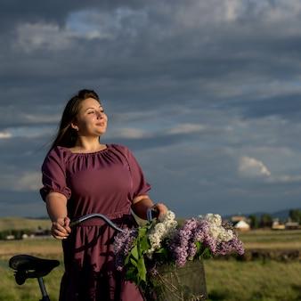 Piękna młoda kaukaska uśmiechnięta szczęśliwa dziewczyna w purpurowej sukni w wianku i na rowerze kosz kwitnącego bzu na wsi na tle dramatycznego nieba. model plus rozmiar. wiosna w stylu rustykalnym