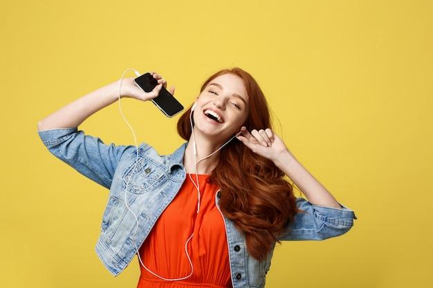 Piękna młoda kędzierzawa czerwona włosiana kobieta słucha muzyka i taniec w hełmofonach.