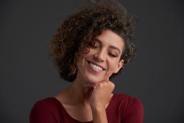 Piękna młoda kędzierzawa kaukaska brunetka pozuje w studiu z zamkniętymi oczami
