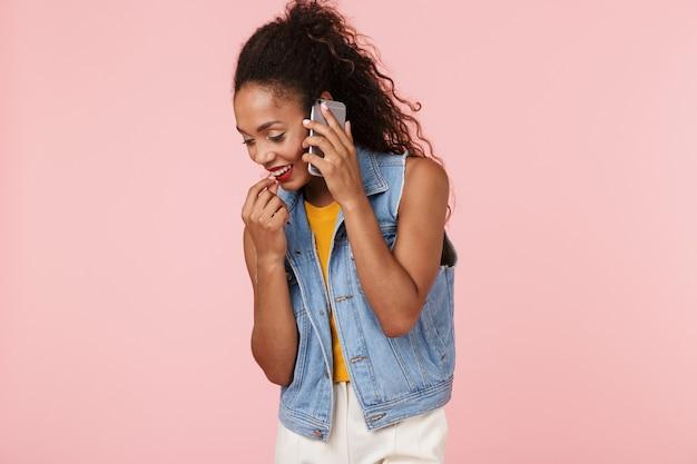 Piękna młoda kobieta afryki na białym tle nad różową ścianą rozmawia przez telefon