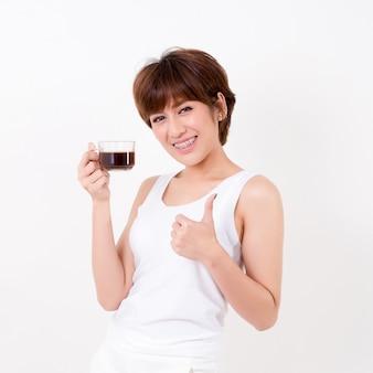 Piękna młoda kobieta asia z filiżanką gorącej kawy. pojedynczo na białym tle. oświetlenie studyjne. koncepcja zdrowego.