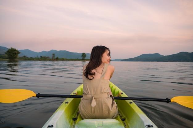 Piękna młoda kobieta azjatyckich gospodarstwa wiosła w kajaku na jeziorze wieczorem na wakacjach. aktywność rekreacyjna, rozrywka rekreacyjna