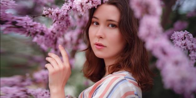 Piękna młoda kobieta azjatyckich korzystających z kwitnących kwiatów na wiosnę. nagi makijaż. portret z bliska