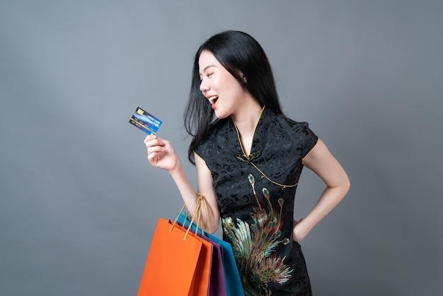Piękna młoda kobieta azjatyckich nosić chiński tradycyjny strój z torbą na zakupy i kartą kredytową na szarej powierzchni