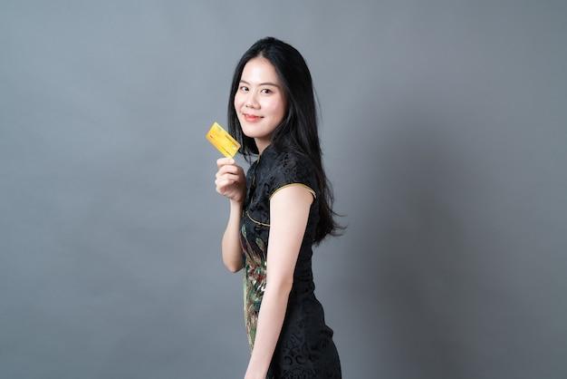 Piękna Młoda Kobieta Azjatyckich Nosić Chiński Tradycyjny Strój Z Torbą Na Zakupy I Kartą Kredytową Premium Zdjęcia