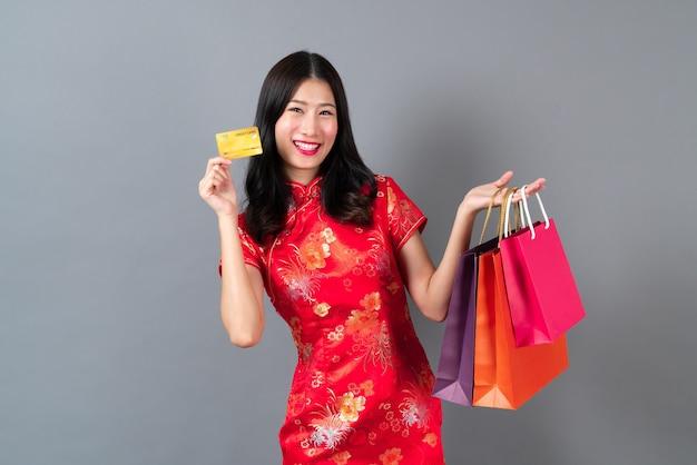 Piękna młoda kobieta azjatyckich nosić czerwony chiński tradycyjny strój z ręką trzymającą kartę kredytową i torby na zakupy