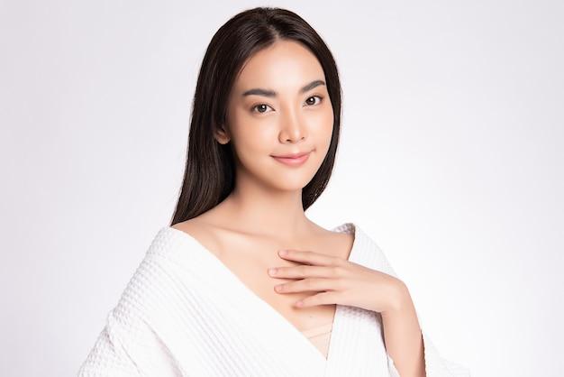 Piękna młoda kobieta azji dotykając jej ciała ze świeżą zdrową skórę, na białym tle