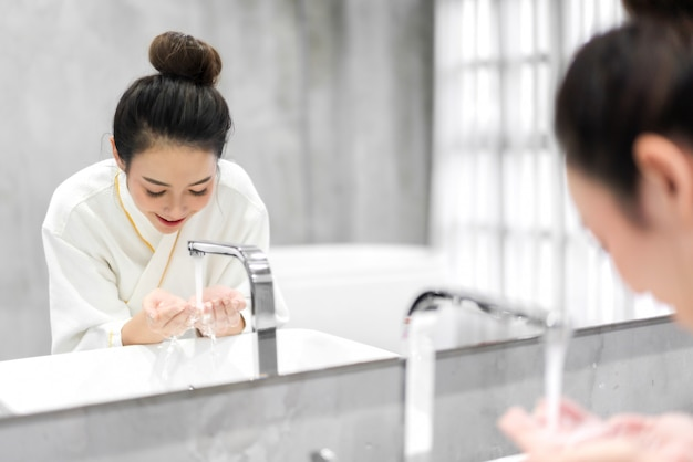 Piękna młoda kobieta azji mycie czystą twarz wodą i uśmiechając się przed lustrem w łazience. piękno i spa. idealna świeża skóra