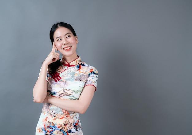 Piękna młoda kobieta azji nosić chiński tradycyjny strój z ręką prezentacji na boku w szarej ścianie