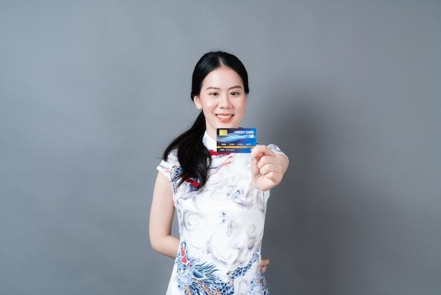 Piękna młoda kobieta azji nosić chiński tradycyjny strój z ręki trzymającej kartę kredytową na szarej powierzchni