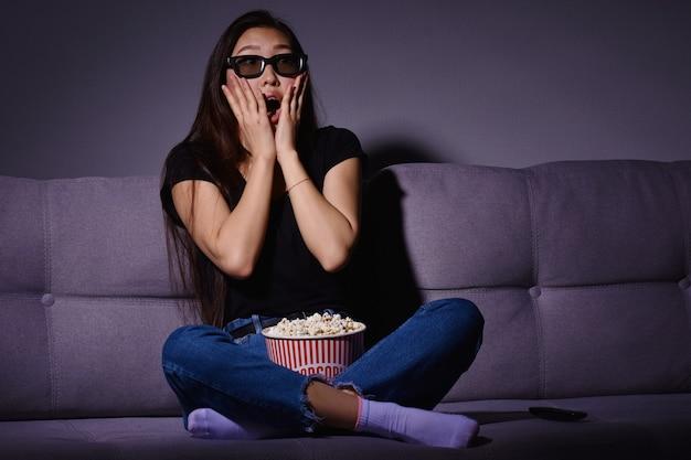 Piękna młoda kobieta azji przed telewizorem w domu. jedzenie popcornu. czas w domu