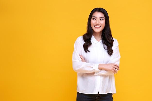 Piękna młoda kobieta azji uśmiechnięta i skrzyżowanymi rękami na żółto.