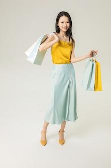 Piękna młoda kobieta azji z torby na zakupy na białym tle