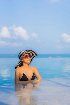 Piękna młoda kobieta azji zrelaksować się wokół basenu w hotelowym kurorcie