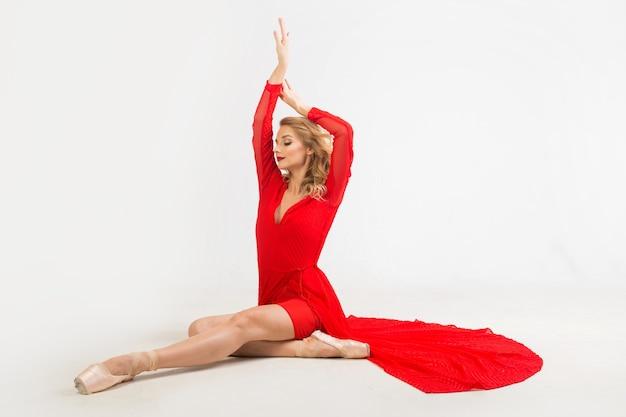 Piękna młoda kobieta baleriny w czerwonej sukience w pozycji siedzącej na białym tle