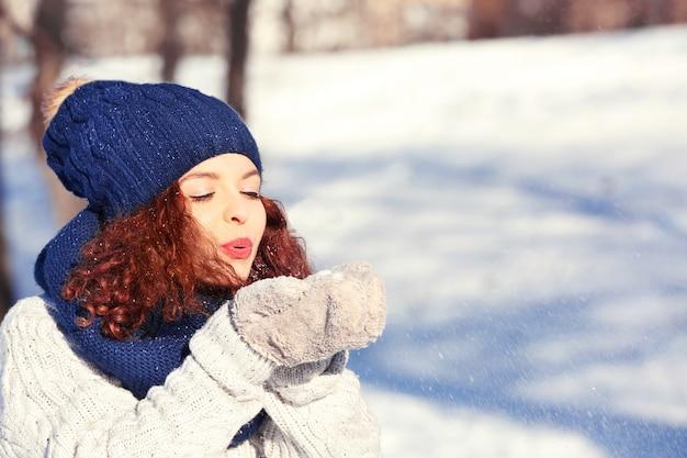 Piękna młoda kobieta bawi się śniegiem na zewnątrz w zimowy dzień
