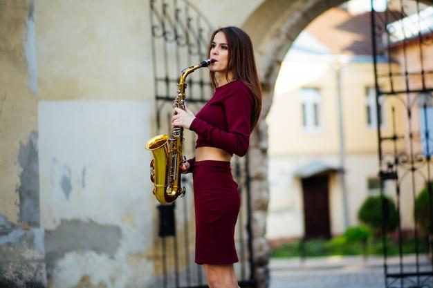 Piękna młoda kobieta bawić się saksofon w ukraina