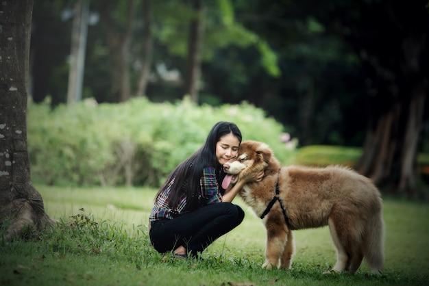 Piękna młoda kobieta bawić się z jej małym psem w parku outdoors. portret stylu życia.