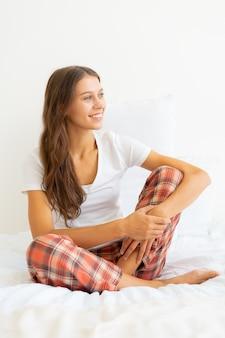 Piękna młoda kobieta bez makijażu, siedząc na łóżku i odwracając wzrok po przebudzeniu.