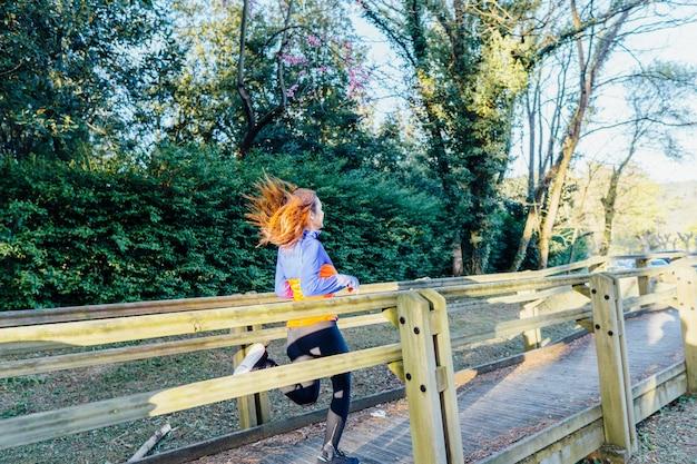 Piękna młoda kobieta biegnąca przez park wiosną lub latem w lesie jest w dół chodnika od tyłu. koncepcja samoopieki sportowej