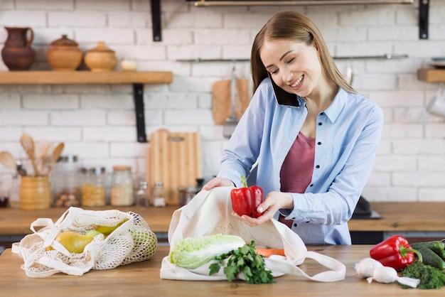 Piękna młoda kobieta bierze artykuły spożywcze z toreb wielokrotnego użytku