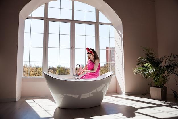 Piękna młoda kobieta bierze kąpiel w dużej stylowej, ceramicznej wannie