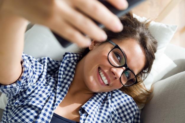 Piękna młoda kobieta bierze selfie w domu.