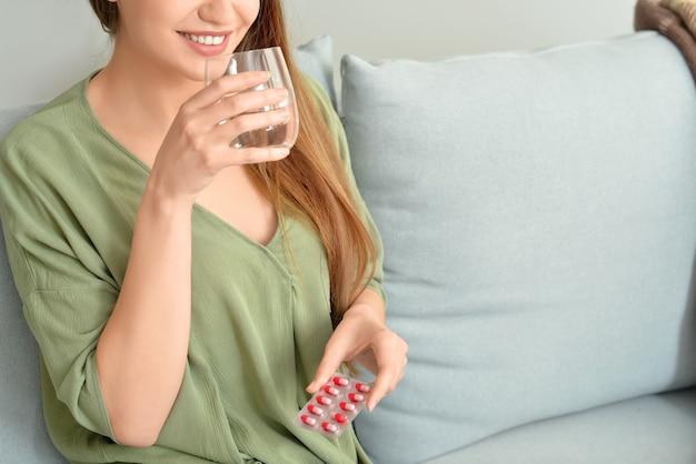 Piękna młoda kobieta biorąc pigułki w domu