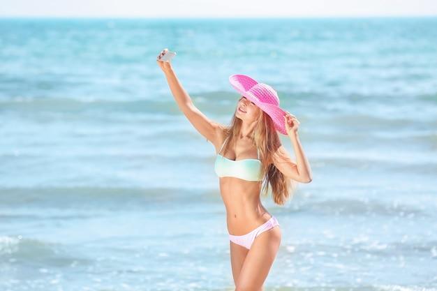 Piękna młoda kobieta biorąc selfie na plaży nad morzem