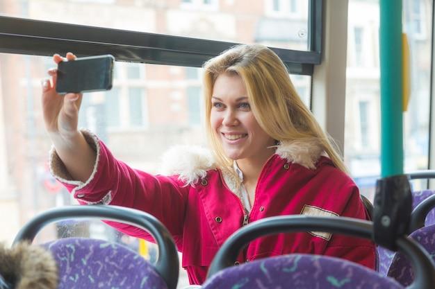 Piękna młoda kobieta biorąc selfie podczas dojazdów do pracy w londynie