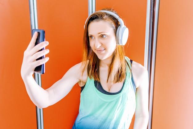 Piękna młoda kobieta, biorąc selfie w szatni siłowni. koncepcja sportowo-technologiczna
