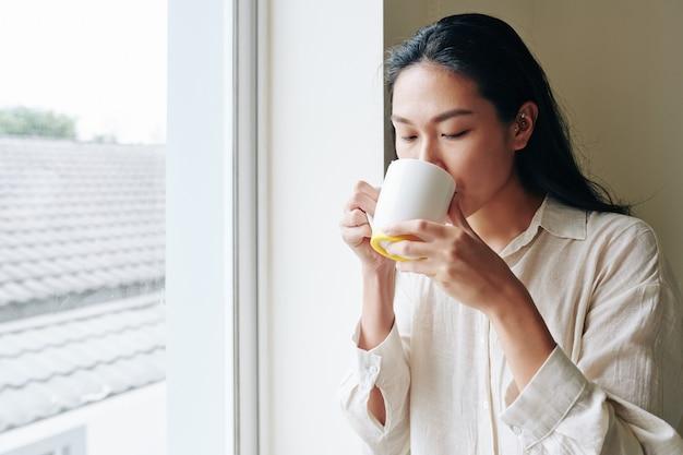 Piękna młoda kobieta chiense, ciesząc się dużym kubkiem porannej kawy, stojąc przy oknie