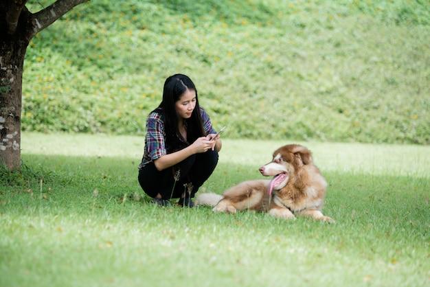 Piękna młoda kobieta chwyta fotografię z jej małym psem w parku outdoors. portret stylu życia.
