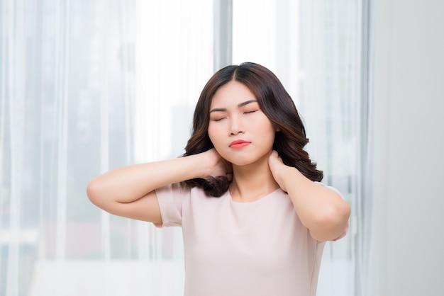Piękna młoda kobieta cierpi na ból szyi