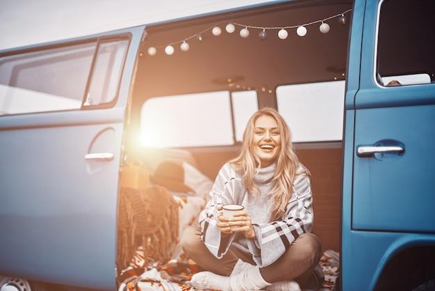 Piękna młoda kobieta, ciesząc się gorącym napojem i uśmiechając się, spędzając czas w retro minivan