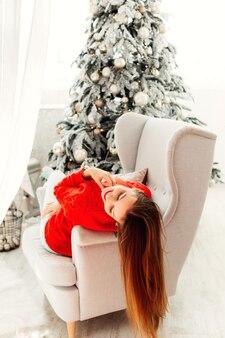 Piękna młoda kobieta cieszy się świątecznym porankiem w swoim fotelu w przytulnym pokoju