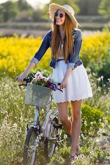 Piękna młoda kobieta cieszy się wiosną w polu.