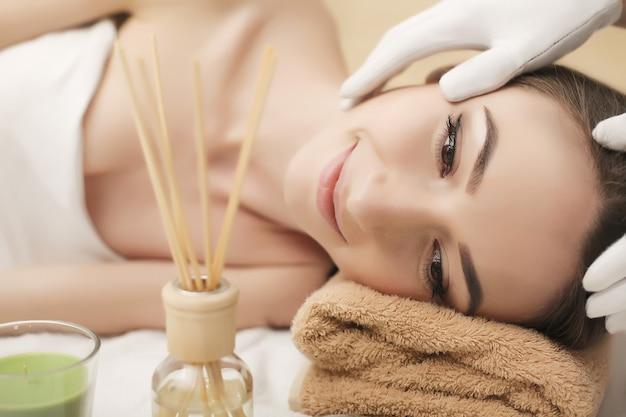 Piękna młoda kobieta coraz masaż twarzy leżąc na kanapie. widok z góry skupiony na twarzy