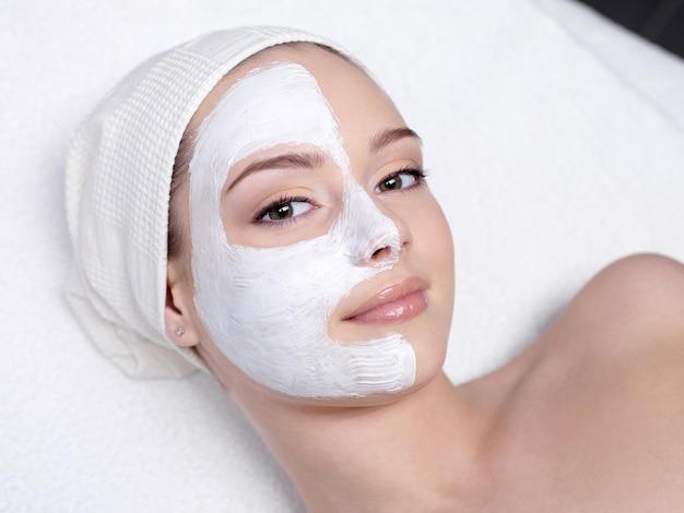 Piękna młoda kobieta coraz maseczka na twarz w salonie kosmetycznym - w pomieszczeniu