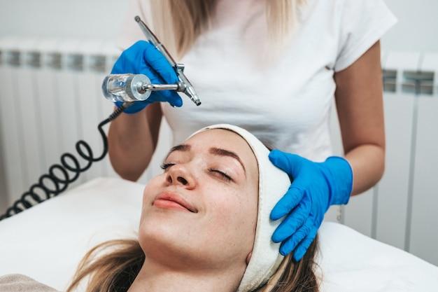 Piękna młoda kobieta coraz zabieg mezoterapii w kosmetycznym gabinecie kosmetycznym.