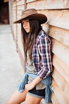 Piękna Młoda Kobieta Cowgirl W Kapeluszu I Koszuli W Kratę Stojąca W Pobliżu Drewnianego Domu Premium Zdjęcia