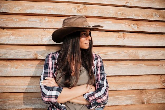 Piękna młoda kobieta cowgirl w kapeluszu stojącym z rękami skrzyżowanymi na drewnianym tle
