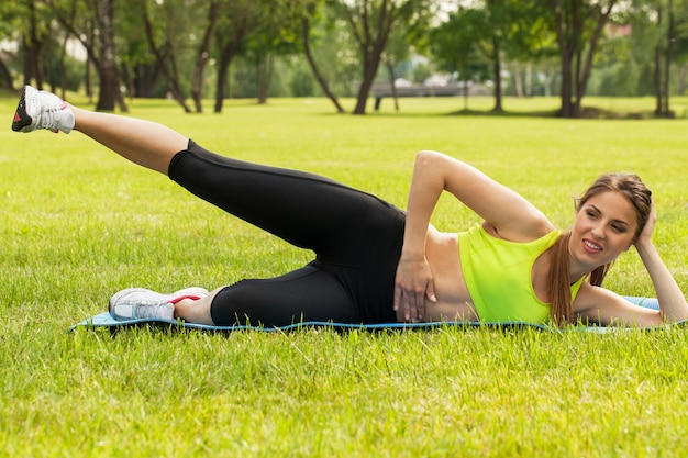 Piękna młoda kobieta ćwiczy na trawie