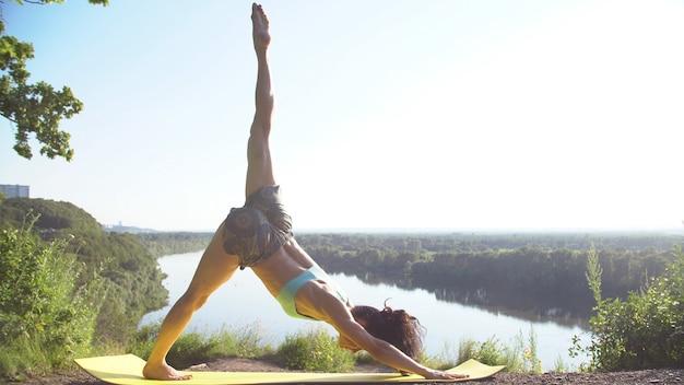 Piękna młoda kobieta ćwiczy ruchy jogi i pozycje na zewnątrz na niesamowitym klifie.