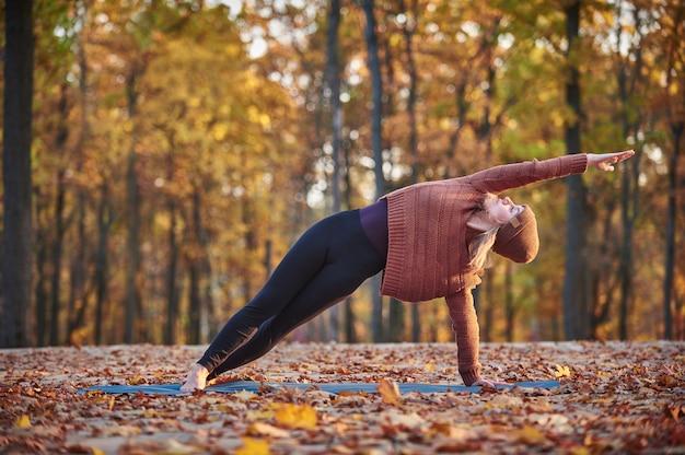 Piękna młoda kobieta ćwiczy zginanie jogi asana vasishthasana na drewnianym pokładzie w parku jesień
