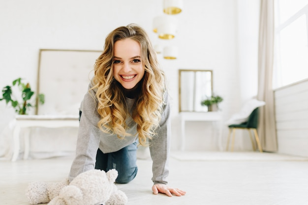 Piękna młoda kobieta czołgać się na podłoga ono uśmiecha się