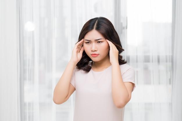Piękna młoda kobieta czuje się chora i ma ból głowy
