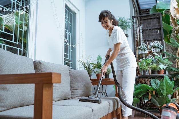 Piękna młoda kobieta czyszczenia odkurzaczem w domu