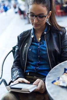 Piękna młoda kobieta czyta książkę na ulicy.